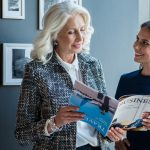 Older, female supervisor discussing business article with younger, female coworker